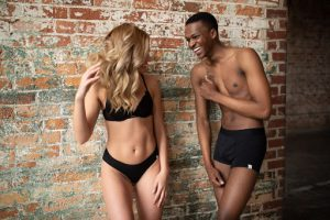 A man and woman stand next to a brick wall and laugh with one another, the man wearing trunks underwear from WAMA.